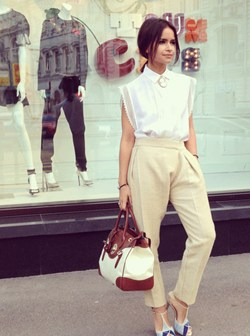 Mira Duma wearing wearing trousers and a shirt from Chloe, Roger Vivier shoes, a Ralph Lauren bag and an antique cameo.